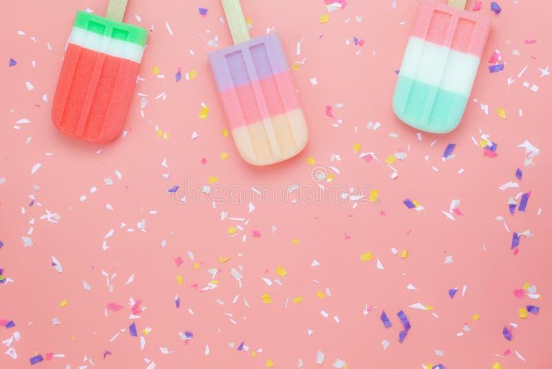 Flacher Lageanordnungsvielzahl-Eiscreme-Knallstock auf moderner rustikaler rosa Papiertapete stockfotos