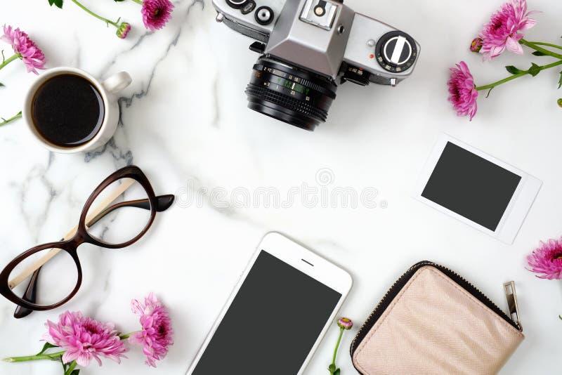 Flacher Lageausgangsschreibtisch Weiblicher Arbeitsplatz mit Handy, Gläser, Weinlesefotokamera, Kaffeetasse, Sofortbild und stockbild
