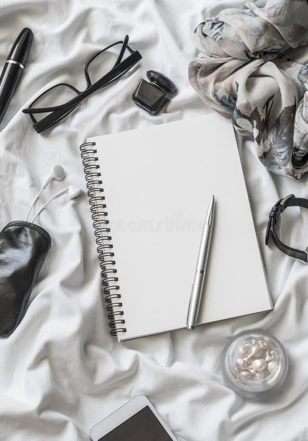 Flacher Lagefrauen-Zubehörhintergrund Leerer Notizblock, Stift, Gläser, Uhr, Wimperntusche, Telefon, Kopfhörer, Parfüm auf einem  lizenzfreies stockfoto