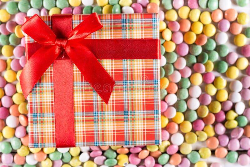 Flacher Lagekasten mit rotem Bogen über bunten runden Süßigkeiten lizenzfreie stockfotografie