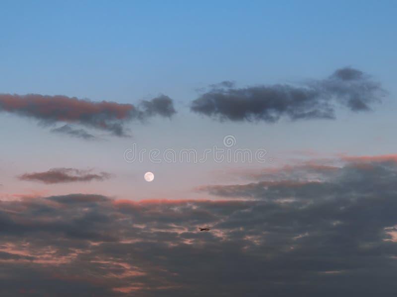 Flaches Fliegen über dem Sonnenunterganghimmel mit Vollmond im Hintergrund stockbilder