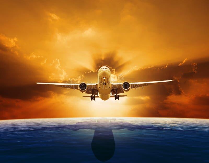 Flaches Fliegen des Passagierflugzeugs über schönem Meeresspiegel mit Sonnensatz stockfotos
