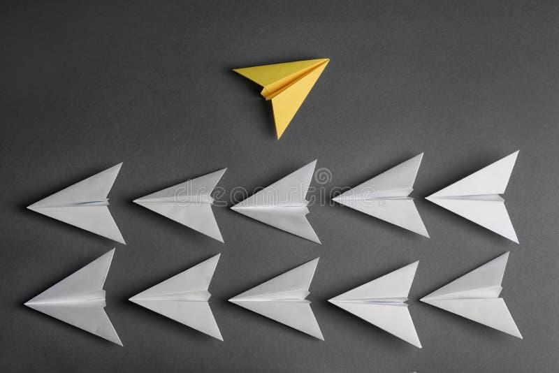 Flaches Fliegen des unterschiedlichen Farbpapiers weg von anderen auf dunklem Hintergrund stockbild