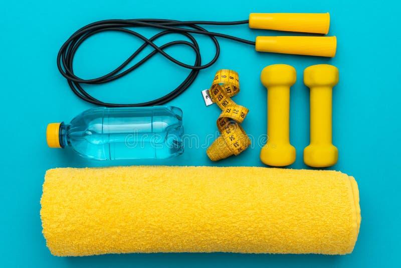 Flaches gelegtes Foto der gelben Eignungsausrüstung in Oder über Türkisblau backgound lizenzfreie stockbilder