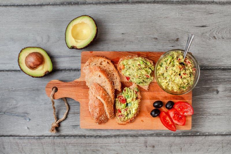 Flaches gelegtes Foto, frisch zubereitetes Guacamole in der kleinen Glasschüssel, Brot, Tomaten, Oliven an Arbeitsbrett und zwei  lizenzfreies stockbild