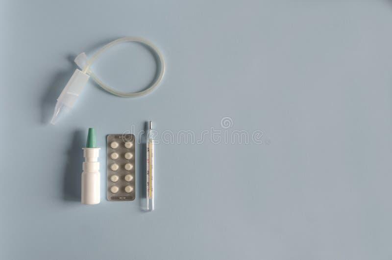 Flaches gelegtes Instrument für das nasale Ausspülen, Quecksilberthermometer, Nasenspray, Tabletten für die Behandlung der Krankh stockfotografie