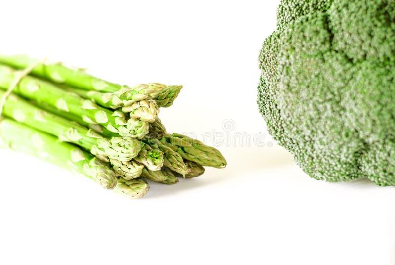Flaches gelegtes Muster des Nahrungsmittelhintergrundspargels und -brokkolis B?ndel frischer gr?ner Spargel auf wei?em Hintergrun stockbild