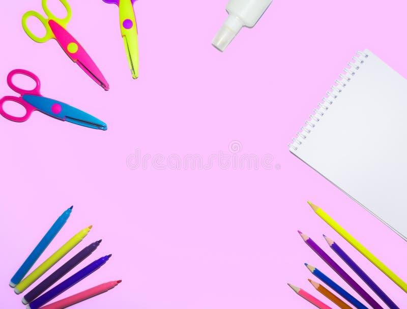Flaches Lagebild von farbigen Bleistiften, von Notizblock und von Scheren zeichnete auf einem Planum eines lokalisierten rosa Hin lizenzfreie stockbilder