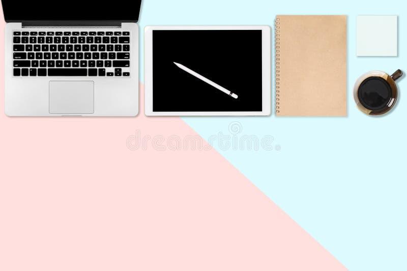 Flaches Lagefoto des Bürotischs mit Laptop-Computer, digitaler Tablette, Handy und Zubehör auf dem modernen Blau mit zwei Tönen u stockfoto