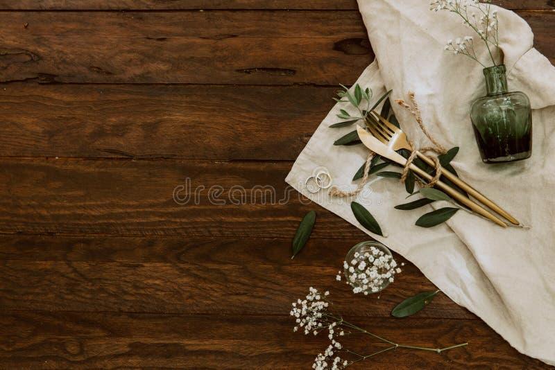 Flaches Lagegoldtischbesteck, Blumen, Ringe auf Leinenserviette, Heiratskonzept, Feiertag blüht auf hölzernem lizenzfreie stockfotos