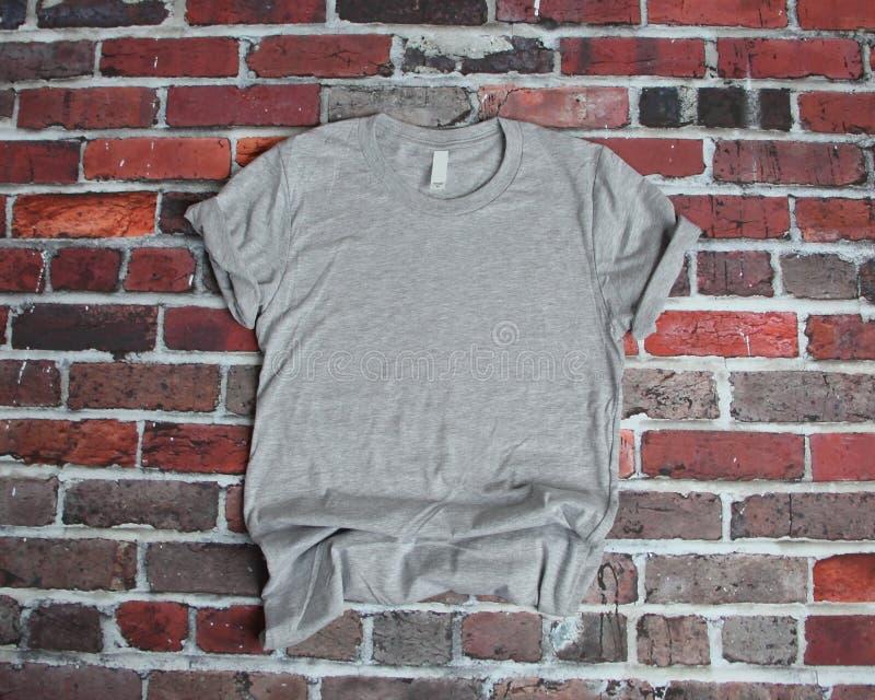 Flaches Lagemodell des grauen T-Shirts auf Ziegelsteinhintergrund lizenzfreie stockfotografie