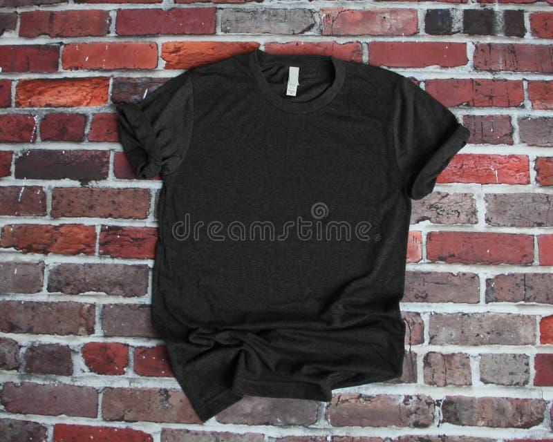 Flaches Lagemodell des koksgrauen T-Shirts auf Ziegelsteinhintergrund lizenzfreies stockbild