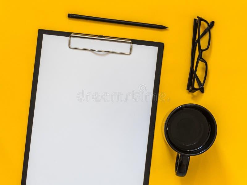 Flaches Lageschwarz-Geschäftszubehör auf gelbem Hintergrund mit Querstation stockfotos