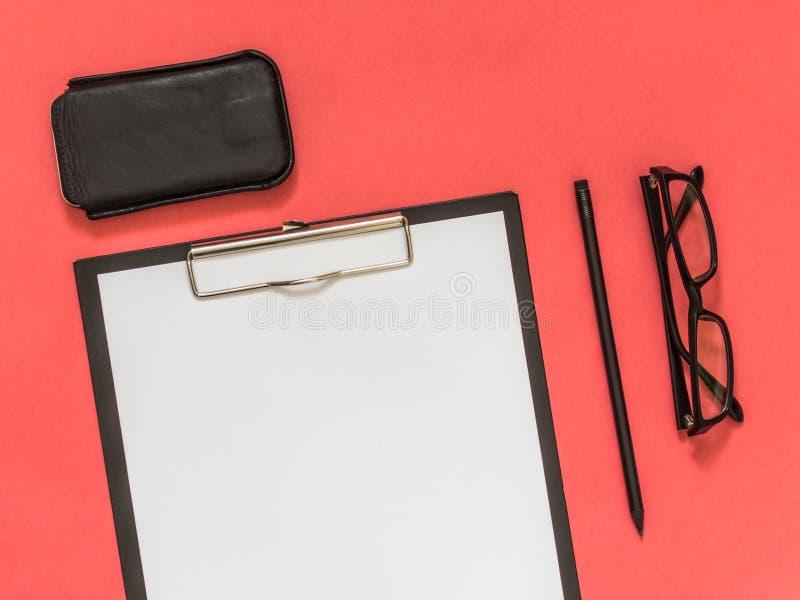 Flaches Lageschwarz-Geschäftszubehör auf rosa Hintergrund mit blan lizenzfreie stockbilder