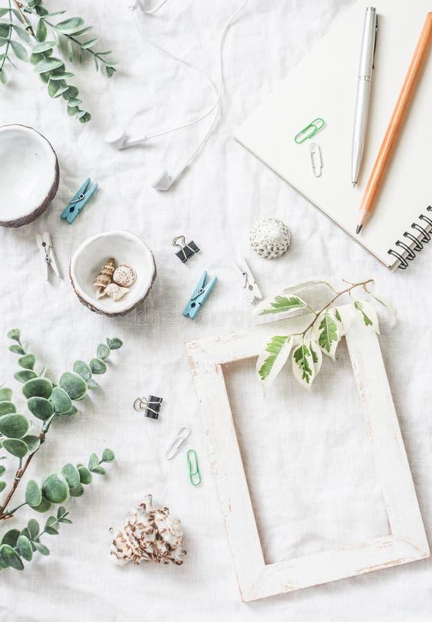 Flaches Lagestillleben der selbst gemachten Handwerksarbeitstabelle mit Zubehör - hölzerner Fotorahmen, Blumen, Muscheln, Bürokla stockbild