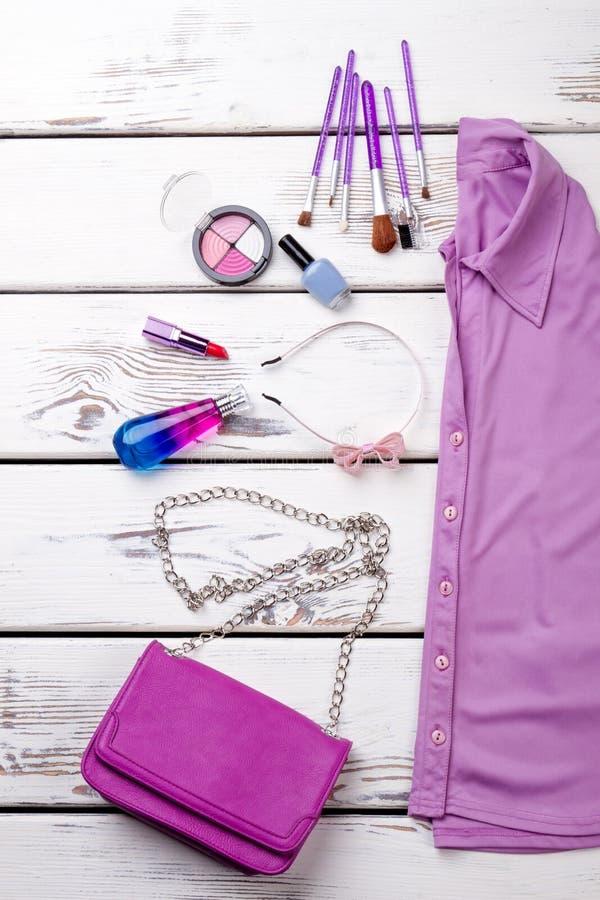 Flaches Lagezubehör für Make-up und violettes Hemd lizenzfreies stockbild