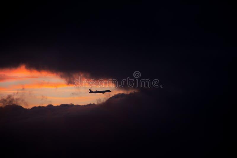 Flaches Schattenbild zwischen Wolken bei Sonnenuntergang stockfoto