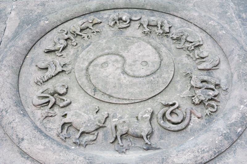 Flachrelief mit YinYang-Symbol und zwölf Tieren stockfotos
