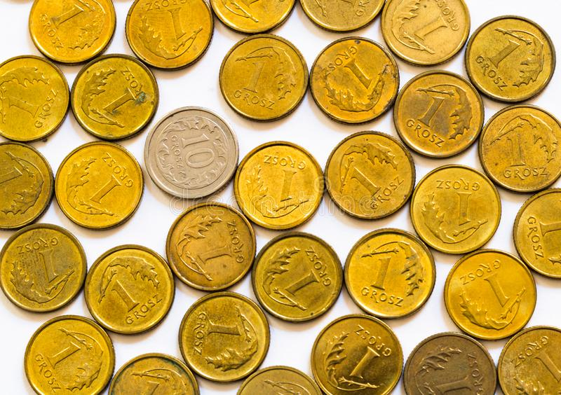 Flackernde Lage der gemischten gelb-gold-polnischen Münzen mit einer Silbermünze mit höherem Nennwert, die auf weißem Hintergrund stockfoto