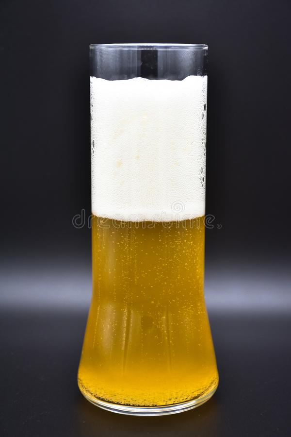 Flacon en verre sur le fond noir avec le liquide jaune et la mousse blanche photographie stock