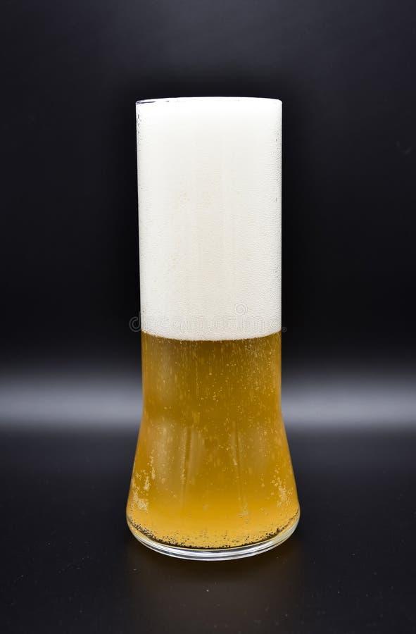 flacon en verre sur le fond noir avec le liquide jaune et la mousse blanche, photos stock