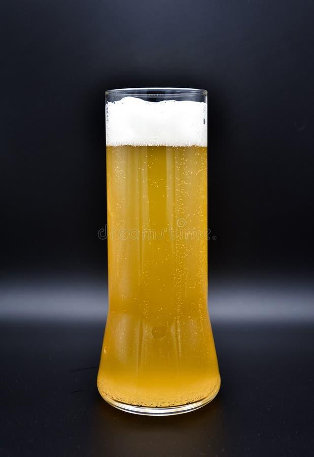 Flacon en verre sur un fond noir avec le liquide jaune et la mousse blanche image libre de droits