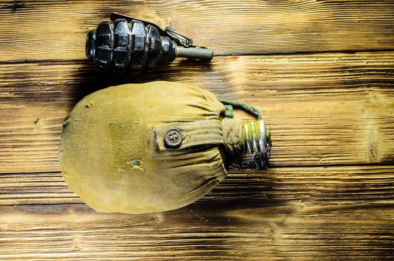 Flacon et grenade à main d'armée sur la table en bois photographie stock
