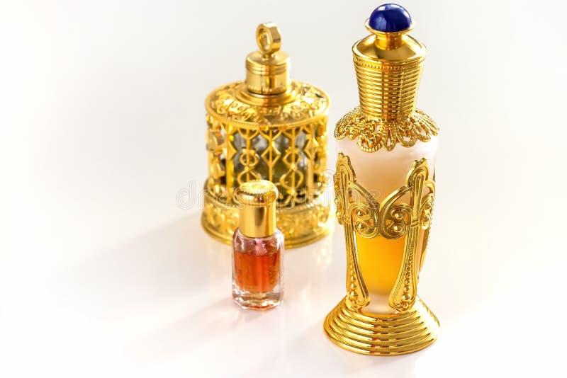 Flacon fleuri d'or traditionnel de parfums Arabes d'huile d'oud Fond blanc d'isolement Copiez l'espace photos stock