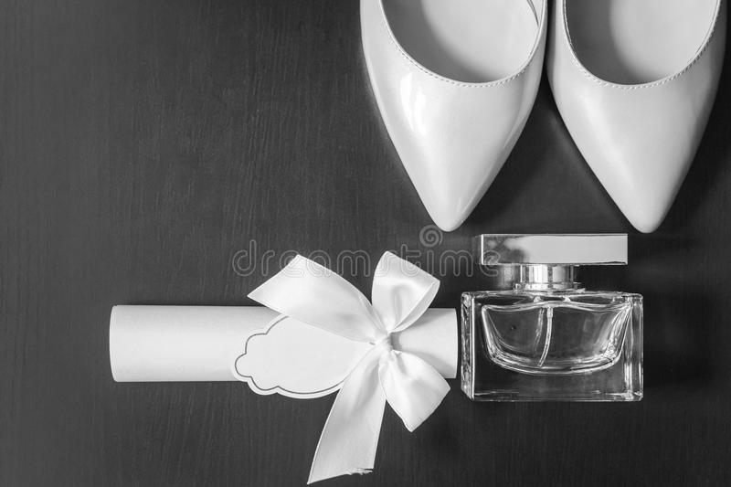 Bottle of perfume near white bridal shoes and box stock images