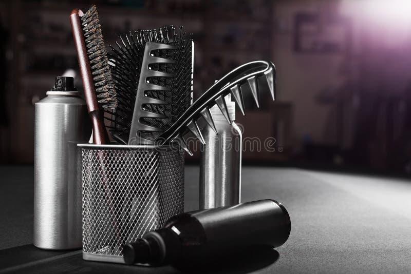 Flacons de lacas para el pelo cerca de una cesta con los cepillos para el pelo fotografía de archivo