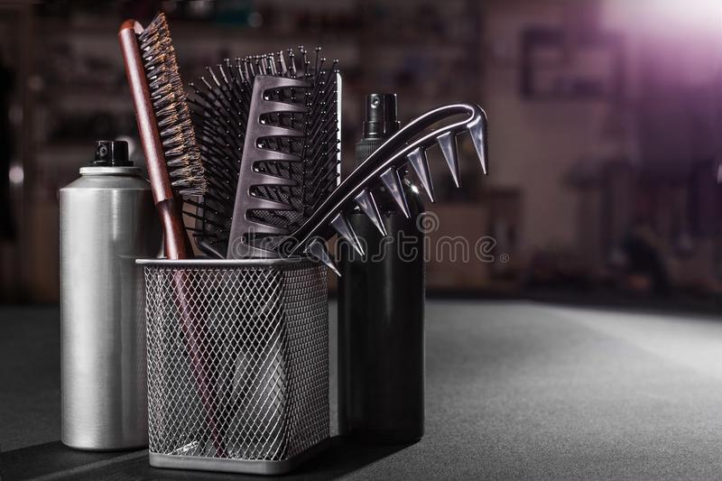 Flacons del pelo que trata los esprayes cerca de una cesta con los peines imagen de archivo libre de regalías