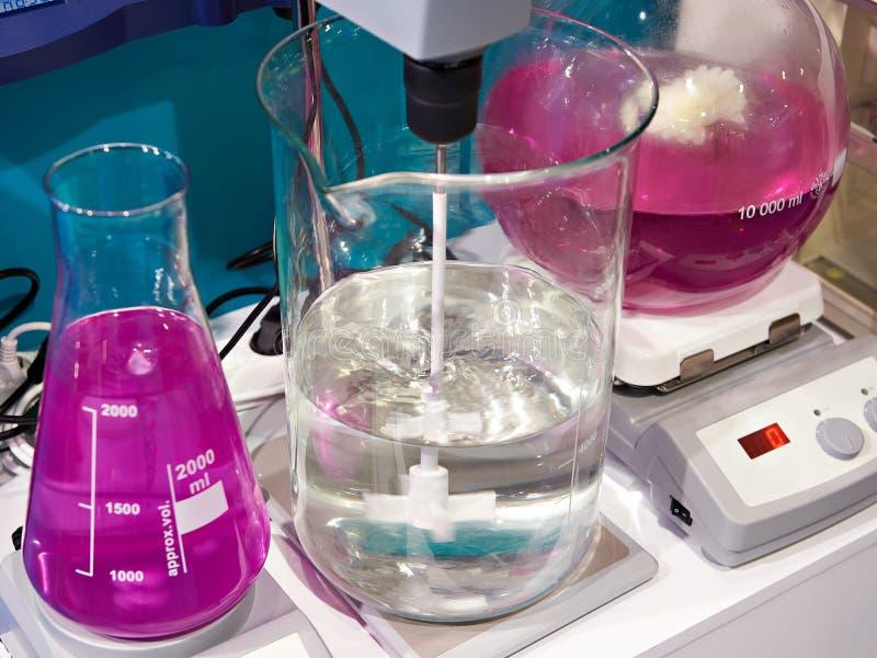 Flacons et dispositifs trembleurs de mélangeur dans le laboratoire chimique image stock