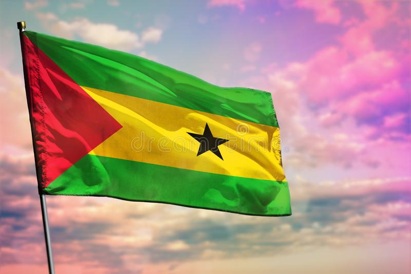 Fladdra den São Tomé och Príncipe flaggan på färgrik bakgrund för molnig himmel V?lst?ndbegrepp royaltyfria bilder