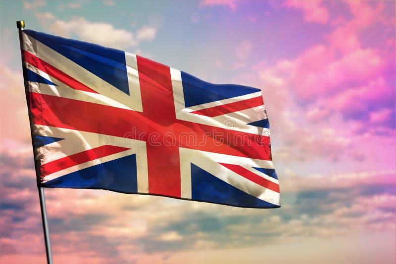 Fladdra Förenade kungariket UK sjunka på färgrik bakgrund för molnig himmel Välståndbegrepp royaltyfri foto