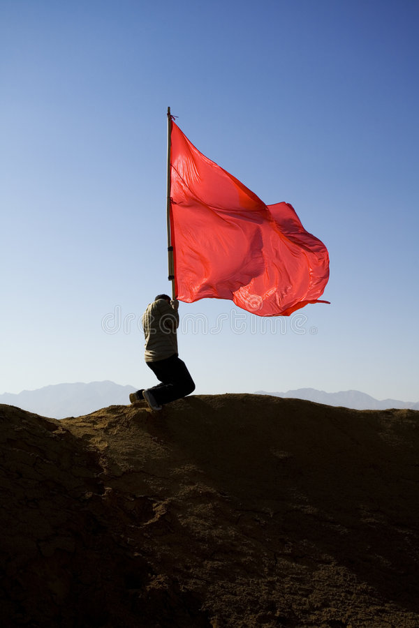 Flag. Man pushing a red flag into the ground