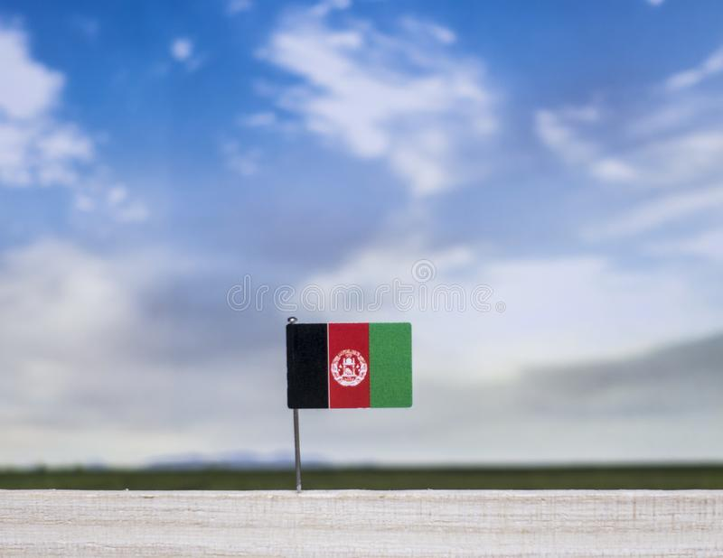 Flag of Afghanistan with vast meadow and blue sky behind it. stock photography