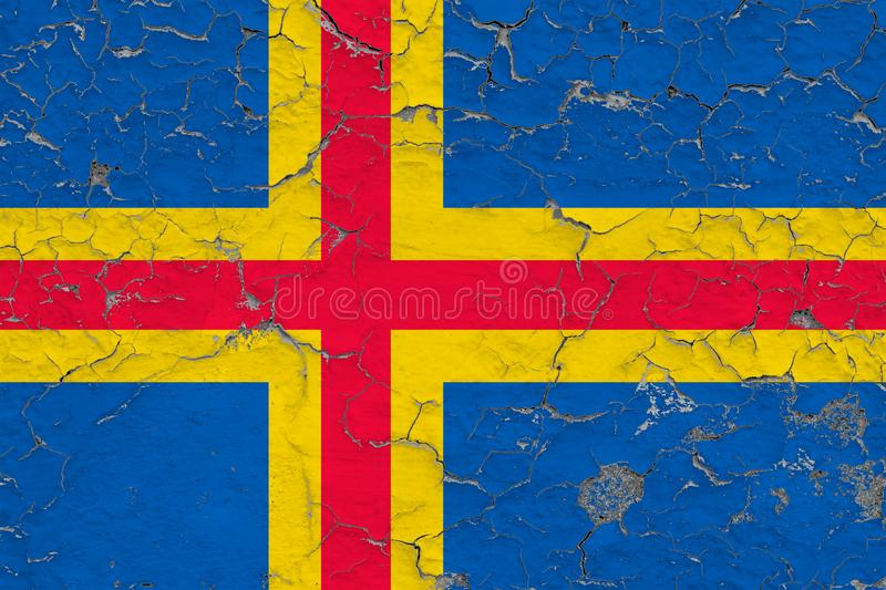 Flag of Aland Islands painted on cracked dirty wall. National pattern on vintage style surface.  royalty free stock images
