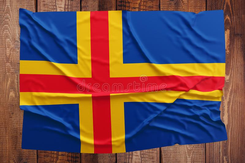 Flag of Aland Islands on a wooden table background. Wrinkled flag top view.  stock photos