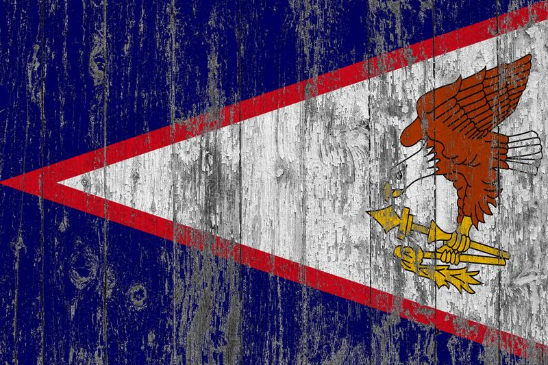 Flag of American Samoa painted on worn out wooden texture background stock image