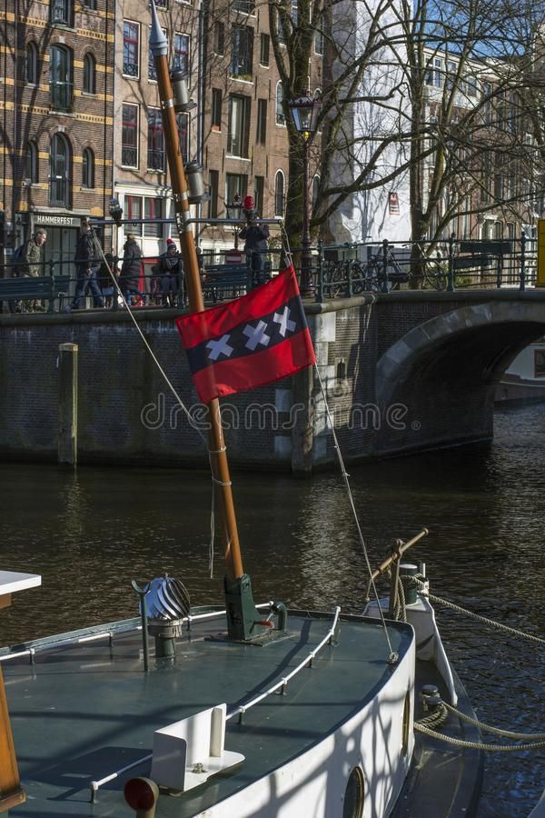 Flag of Amsterdam on a boat near the bridge in the historical center of Amsterdam in the autumn. Sunny day royalty free stock photography