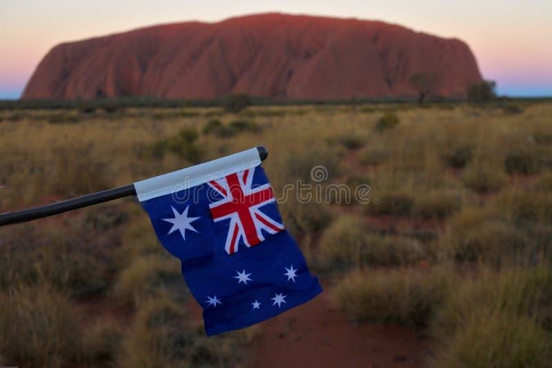 Flag of Australia against Uluru Ayers Rock at sunset Uluru-Kata Tjuta National Park Northern Territory Australia royalty free stock photo