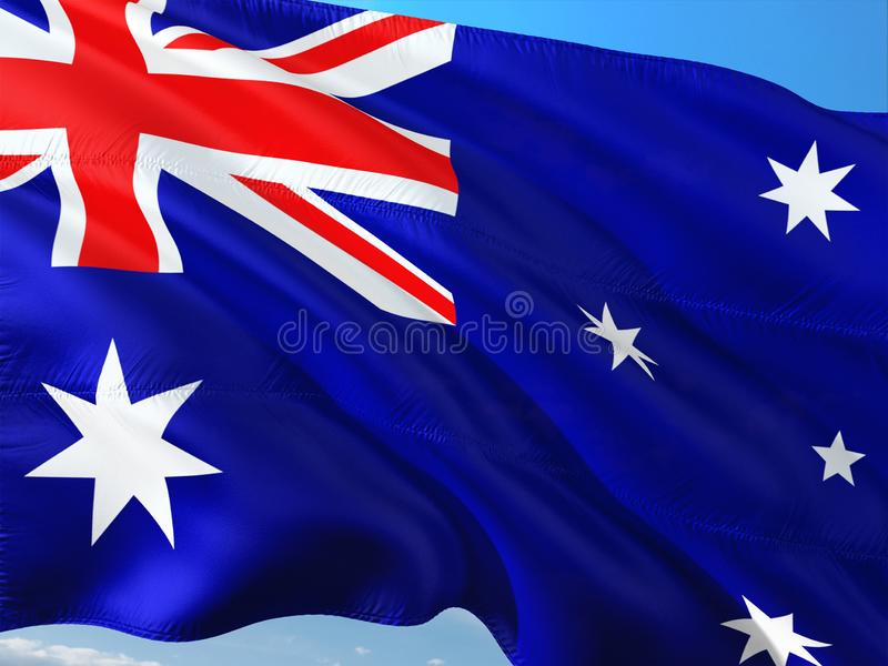Flag of Australia waving in the wind against deep blue sky. High quality fabric.  stock photos