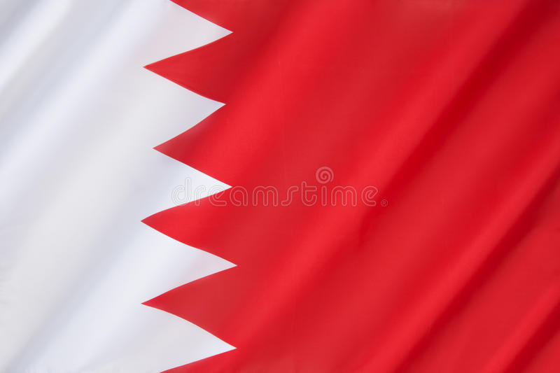 Flag of Bahrain. The national flag of Bahrain consists of a white band on the left, separated from a red area on the right by five triangles that serve as a royalty free stock image