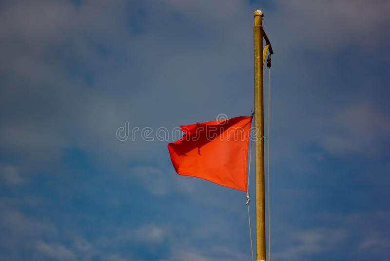 flag on the beach indicating the rescue station that houses the red lifeguards stock photos
