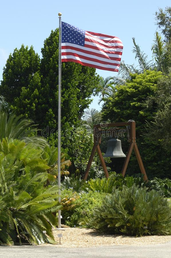 Flag and bell in a garden royalty free stock photos