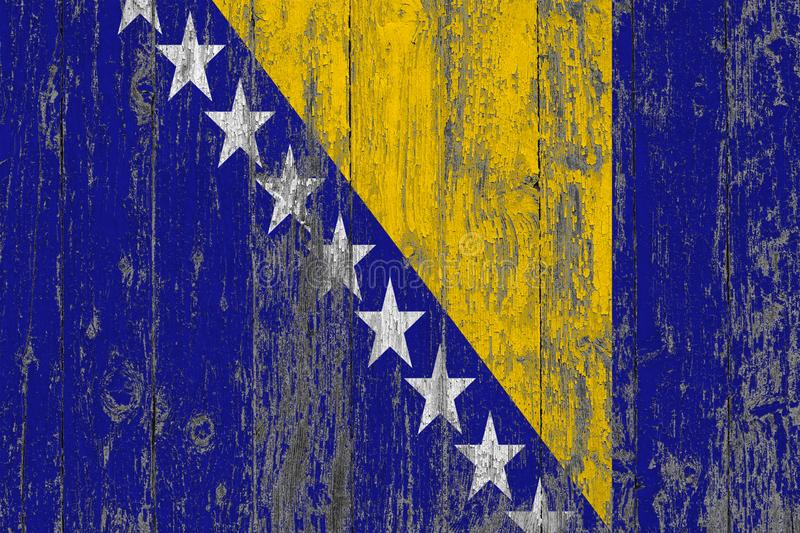 Flag of Bosnia Herzegovina painted on worn out wooden texture background.  stock photos
