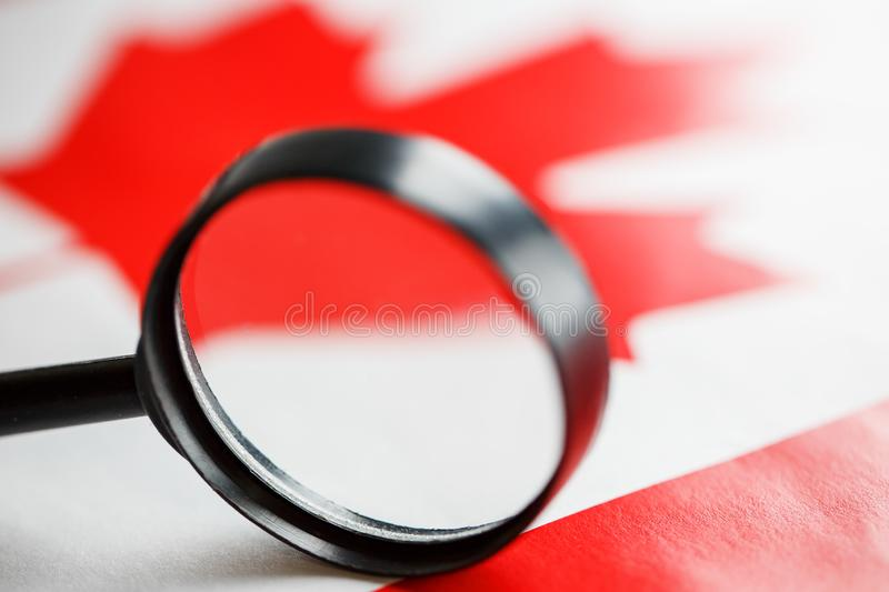 The flag of CANADA is looked through a magnifying glass. Espionage and surveillance of Canada. Monitoring the status of Kanatsev stock photos