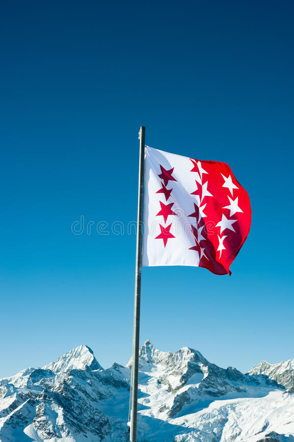 Flag of canton Wallis, Switzerland. With snow mountains in the background, Zermatt, Switzerland royalty free stock photo