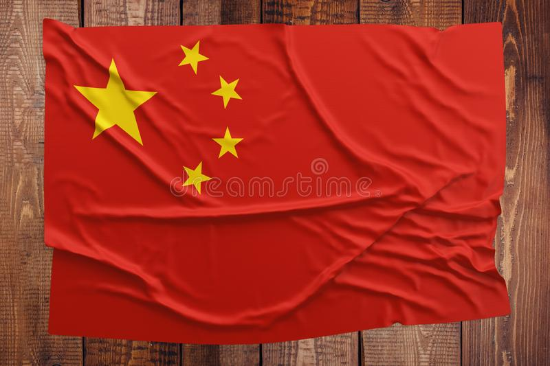 Flag of China on a wooden table background. Wrinkled Chinese flag top view.  stock photography