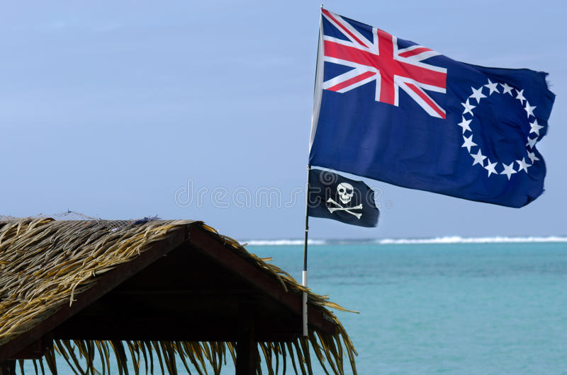 Flag of the Cook Islands. The Cook Islands national flag and Jolly Roger pirates flag wave in the wind at Muri Lagoon in Rarotonga Cook Islands royalty free stock photo